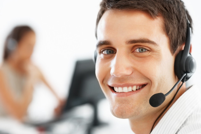 Closeup of smiling customer service executive with headphones